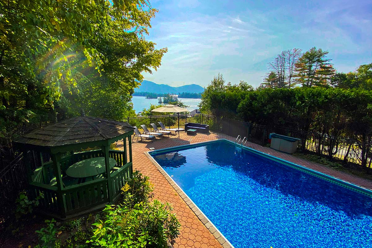 In-ground pool with views of Lake George